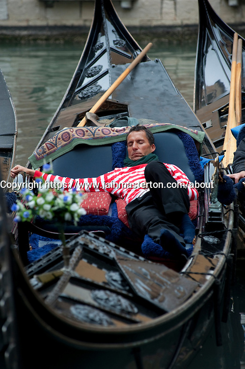 Gondolier sleeping in his gondola on canal in Venice Italy