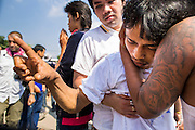 "23 MARCH 2013 - NAKHON CHAI SI, NAKHON PATHOM, THAILAND:  A man is restrained by a friend after he went into a trance at the end of the Wat Bang Phra tattoo festival. Wat Bang Phra is the best known ""Sak Yant"" tattoo temple in Thailand. It's located in Nakhon Pathom province, about 40 miles from Bangkok. The tattoos are given with hollow stainless steel needles and are thought to possess magical powers of protection. The tattoos, which are given by Buddhist monks, are popular with soldiers, policeman and gangsters, people who generally live in harm's way. The tattoo must be activated to remain powerful and the annual Wai Khru Ceremony (tattoo festival) at the temple draws thousands of devotees who come to the temple to activate or renew the tattoos. People go into trance like states and then assume the personality of their tattoo, so people with tiger tattoos assume the personality of a tiger, people with monkey tattoos take on the personality of a monkey and so on. In recent years the tattoo festival has become popular with tourists who make the trip to Nakorn Pathom province to see a side of ""exotic"" Thailand. The 2013 tattoo festival was on March 23.   PHOTO BY JACK KURTZ"