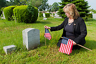 MAY 28, 2011 - UNIONDALE, NY: Claudia Borecky placing flags at tombstones of US Veterans at Town of Hempstead's Greenfield Cemetery, Saturday morning of Memorial Day Weekend, on May 28, 2011, in Uniondale, New York, USA.
