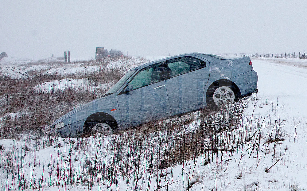 © Licensed to London News Pictures. 27/01/2012. Derbyshire, UK. A car  left abandoned in a ditch along Peak District's notorious Snake Pass Road between Manchester and Sheffield on January 27th, 2012, following heavy snow fall. Photo credit : Joel Goodman/LNP