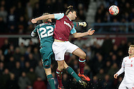 Goalkeeper Simon Mignolet of Liverpool punches the ball past Andy Carroll of West Ham United The Emirates FA cup, 4th round replay match, West Ham Utd v Liverpool at the Boleyn Ground, Upton Park  in London on Tuesday 9th February 2016.<br /> pic by John Patrick Fletcher, Andrew Orchard sports photography.