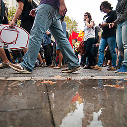 Reflections are cast in a puddle as students past during a protest against educational cuts.