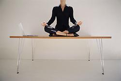 Dec. 05, 2012 - Woman meditating on desk (Credit Image: © Image Source/ZUMAPRESS.com)