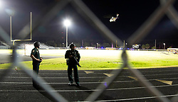August 18, 2018 - Wellington, Florida, U.S. - Police men stand guard as Trauma Hawk lands on the field at Palm Beach Central High School to transports a shooting victim. Two adults were shot Friday night at a football game between Palm Beach Central and William T. Dwyer high schools, authorities said. The gunfire sent players and fans screaming and stampeding in panic during the fourth quarter of the game at Palm Beach Central High School in Wellington, Florida on August 17, 2018. (Credit Image: © Allen Eyestone/The Palm Beach Post via ZUMA Wire)