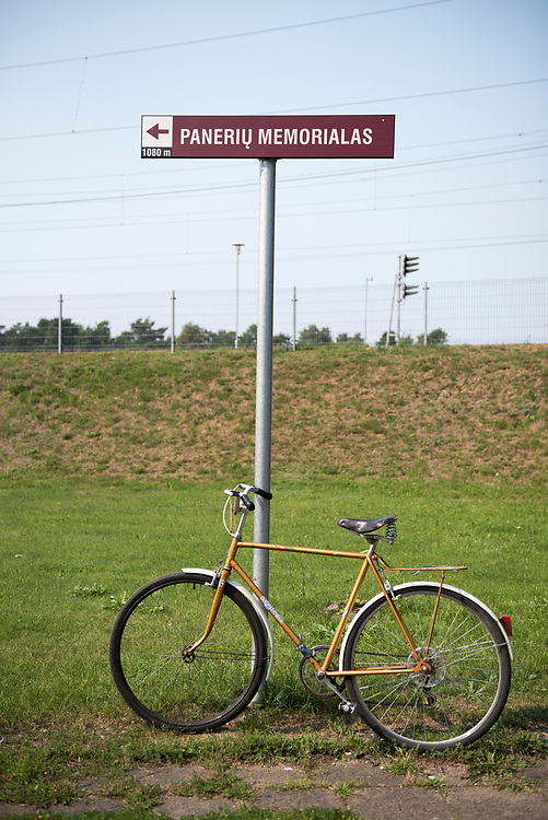 Paneriai, Lithuania - August 12, 2015: A bicycle is parked at a sign pointing the direction to the Paneriai memorial museum in Paneriai (Ponary), Lithuania. Paneriai is where an estimated 100,000 people, mostly Jews but also Poles and Russians, were exacuted at the hands of the Nazis during World War II.
