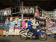 02 SEPTEMBER 2015 - BANGKOK, THAILAND: A man and his daughter go past the back entrance into Bang Chak Market on his motorscooter. The Bang Chak Market serves the community around Sois 91-97 on Sukhumvit Road in the Bangkok suburbs. About half of the market has been torn down, vendors in the remaining part of the market said they expect to be evicted by the end of the year. The old market, and many of the small working class shophouses and apartments near the market are being being torn down. People who live in the area said condominiums are being built on the land.         PHOTO BY JACK KURTZ