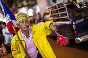 """20 DECEMBER 2013 - BANGKOK, THAILAND: An elderly anti-government protestor walks down Silom Road. Thousands of anti-government protestors, supporters of the so called Peoples Democratic Reform Committee (PRDC), jammed the Silom area, the """"Wall Street"""" of Bangkok, Friday as a part of the ongoing protests against the caretaker government of Yingluck Shinawatra. Yingluck dissolved the Thai Parliament earlier this month and called for national elections on Feb. 2, 2014. The protestors want the elections postponed and the caretaker government to step down. The Thai election commission ruled Friday that the election would go on dispite the protests.          PHOTO BY JACK KURTZ"""