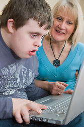 Mother and teenage son with Downs Syndrome using a laptop computer,