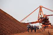 Workers walk by piles of iron ore at a transfer and storage center operated by the Shanghai International Port Group in Shanghai, China on 26 January 2010. China's economic boom and hunger for natural resources has been a blessing for countries such as Australia and Brazil, who controls most the world's high quality iron ore deposits.