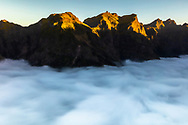 Mountain peaks shined by the sun over the clouds