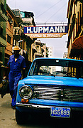 Street scene with old car and cuban man leaving tobacco factory.