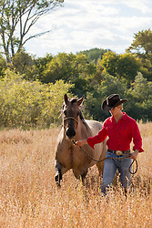 All American cowboy walking with a horse in a field