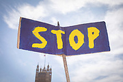 A blue and yellow Stop placard during  the Stop The Coup protest against the proroguing of Parliament on 31st August 2019 in London in the United Kingdom. Left-wing group Momentum and the Peoples Assembly coordinated a series of Stop The Coup protests across the UK today, aimed at Boris Johnson and the UK government proroguing Parliament.