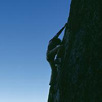 Sierra Nevada, California. Rock climber bouldering on Buttermilk Rocks near Bishop.