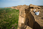 Tourists relax on the border of the cliff in the Bandiagara Escarpment. The Dogon Country is the most visited part of Mali with tourists visiting its tipical  villages that can be located on the cliff, on the sandy plain or in the rocky plateau