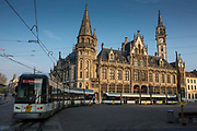 modern De Lijn tramcar travels on the tram network past the historic building of the Old Post Office, Ghent, Belgium with a clear blue sky and sunshine.