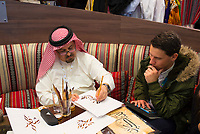 DEU, Deutschland, Germany, Berlin, 07.03.2019: Internationale Tourismus-Börse (ITB) auf dem Berliner Messegelände. Am Stand des Emirats Sharjah (UAE) schreibt ein Kalligraph den Namens eines Besuchers auf Arabisch.