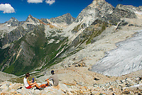 Hikers resting on summit of Glacier Crest Trail and gazing at Illecilleweat Glacier and Mount Sir Donald, Glacier National Park British Columbia Canada