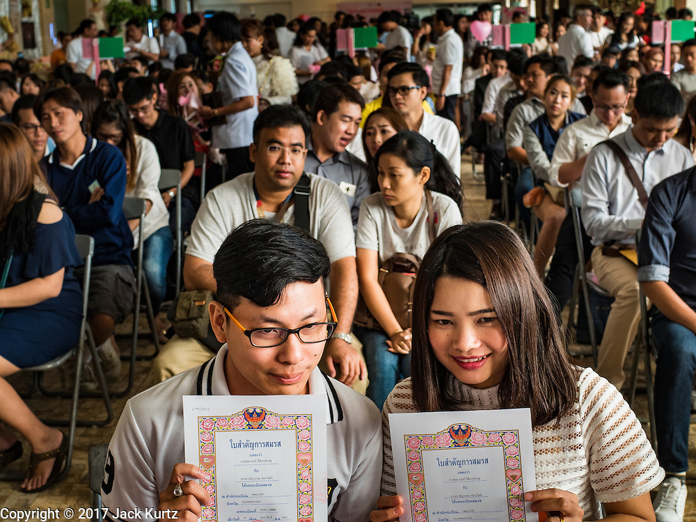 """14 FEBRUARY 2017 - BANGKOK, THAILAND:  A couple holds up their wedding registrations in the Bang Rak district in Bangkok. Bang Rak is a popular neighborhood for weddings in Bangkok because it translates as """"Village of Love."""" (Bang translates as village, Rak translates as love.) Hundreds of couples get married in the district on Valentine's Day, which, despite its Catholic origins, is widely celebrated in Thailand.     PHOTO BY JACK KURTZ"""
