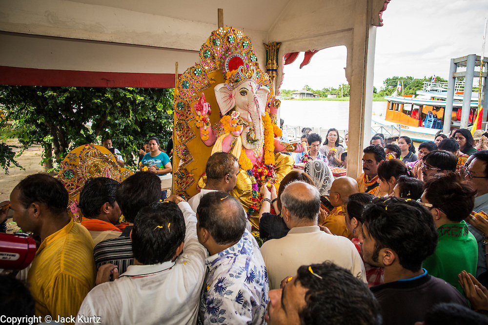 """15 SEPTEMBER 2013 - BANGKOK, THAILAND: Hindus in Bangkok sing and pray on the last day of Ganesha Chaturthi celebrations at Shiva Temple in Bangkok. Ganesha Chaturthi is the Hindu festival celebrated on the day of the re-birth of Lord Ganesha, the son of Shiva and Parvati. The festival, also known as Ganeshotsav (""""Festival of Ganesha"""") is observed in the Hindu calendar month of Bhaadrapada. The festival lasts for 10 days, ending on Anant Chaturdashi. Ganesha is a widely worshipped Hindu deity and is revered by many Thai Buddhists. Ganesha is widely revered as the remover of obstacles, the patron of arts and sciences and the deva of intellect and wisdom. The last day of the festival is marked by the immersion of the deity, which symbolizes the cycle of creation and dissolution in nature.  In Bangkok, the deity (statue) was submerged in the Chao Phraya River.         PHOTO BY JACK KURTZ"""
