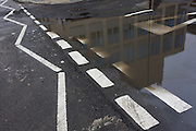 Rdmains of rain covering road markings on a south London street corner.