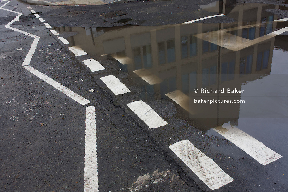 Rdmains of rain covering road markings on a south London street corner.