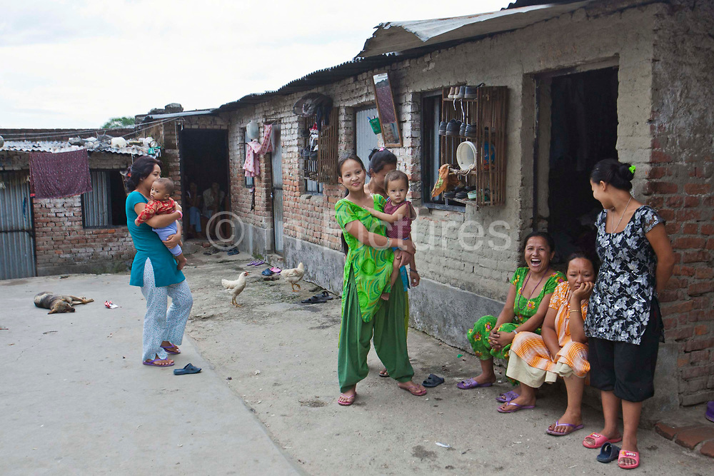 Women and young children in the courtyard of the living quarters of R.C Rug factory in Narayanthan area of Kathmandu, Nepal.  The company has been assessed by the GoodWeave Foundation and found to have excellent quality and fair conditions for its workers. The carpet factory industry in Nepal is notorious for poor working conditions and forcing young children into labour.