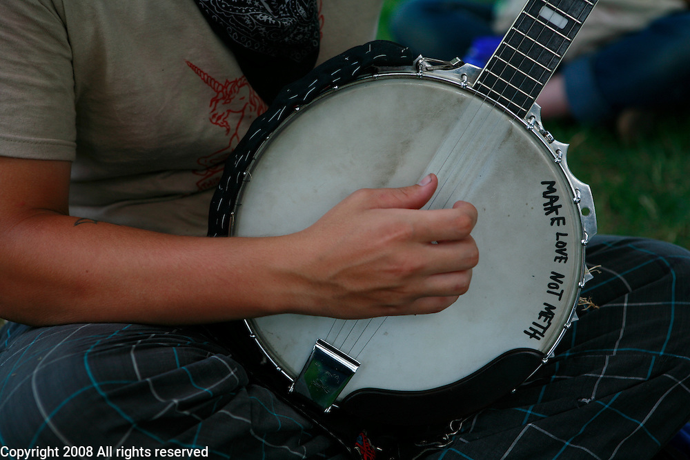 A punk from Canada plays a banjo in a music circle during the Plan-It-X Festival.