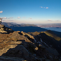 A backpacker summits Lincoln Peak in Glacier National Park to cast a miles-long shadow at sunrise.