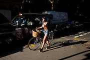 Young woman pushes her bicycle along the pavement after dismounting and walking in heavy afternoon London traffic.