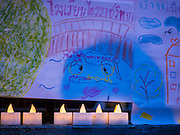 21 AUGUST 2015 - BANGKOK, THAILAND:  Small electric candles and children's art work left as a memorial at the Erawan Shrine Friday. The Bangkok Metropolitan Administration (BMA) held a religious ceremony Friday for the Ratchaprasong bomb victims. The ceremony started with a Brahmin blessing at Erawan Shrine, which was the target of a bombing Monday night. After the blessing people went across the street to the plaza in front of Central World mall for an interfaith religious service. Theravada Buddhists, Mahayana Buddhists, Muslims, Sikhs, Hindus, and Christians participated in the service. Life at the shrine, one of the busiest in Bangkok, is returning to normal. Friday the dancers and musicians who perform at the shrine resumed their schedules.        PHOTO BY JACK KURTZ