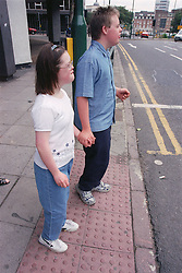 Teenage boy and girl with Downs Syndrome holding hands and waiting to cross road at pedestrian crossing,