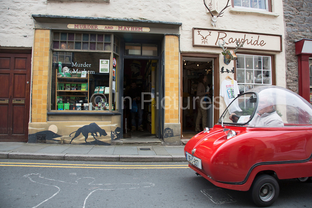 "Rare Maserati vintage Peel Bubble Car passes the Murder and Mayhem crime book shop in Hay-on-Wye or Y Gelli Gandryll in Welsh, known as ""the town of books"", is a small town in Powys, Wales famous for it's many second hand and specialist bookshops, although the number has declined sharply in recent years, many becoming general antique shops and similar."