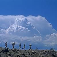 As a summer thunderstorm approaches, an adventure racing team runs along a desert ridge in southern Arizona.