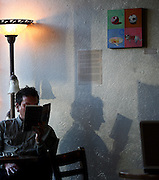 SHOT 11/27/2007 - Photos of Highland Square shopping and dining in Denver, Co. near 32nd Ave. and Lowell. A customer casts a shadow on a wall as he reads a book at Common Grounds, a coffee house near 32nd and Lowell. Proximity to downtown led to rapid growth of the area in recent years, while the area today is one of the more sought-after city-center neighborhoods. Consequently, considerable redevelopment is occurring in Highland along with a noticeable rise in density, as high-end condominiums and lofts replace older structures and parking lots. However, Highland still offers a large stock of historic single family homes -- now some of the closest historic single family construction to Denver's original town site on the South Platte River..(Photo by Marc Piscotty/ © 2007)