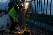A Lambeth council contractor repairs park railings by welding uprights. With sparks flaring, fall and bounce off the pavement from his equipment on the ground. The man has been employed by Lambeth council to repair the railings that surround Ruskin Park, a public space in this south London borough. The workman uses Oxy-fuel welding (commonly called oxyacetylene welding, oxy welding, or gas welding in the U.S.) and oxy-fuel cutting are processes that use fuel gases and oxygen to weld and cut metals, respectively.