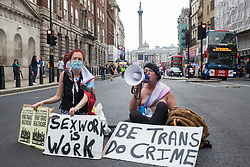 London, UK. 24th July, 2021. Trans rights campaigners sit in Whitehall as the first-ever Reclaim Pride march approaches. Reclaim Pride replaced the traditional Pride in London march, which many feel has become too commercial and strayed from its roots in protest, and was billed as a People's Pride march for LGBTI+ liberation.