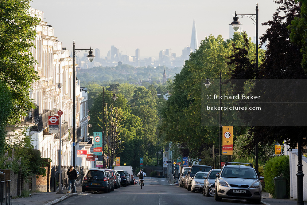 With the London skyline in the far distance, a cyclist descends the steep Gypsy Hill in Crystal Palace, on 16th June 2021, in London, England.