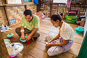 03 MARCH 2104 - MAE KASA, TAK, THAILAND:  A TB patient and her husband eat lunch in their home at the Sanatorium Center for Border Communities in Mae Kasa, about 30 minutes north of Mae Sot, Thailand. The Sanatorium provides treatment and housing for people with tuberculosis in an isolated setting for about 68 patients, all Burmese. The clinic is operated by the Shoklo Malaria Research Unit and works with several other NGOs that assist Burmese people in Thailand. Reforms in Myanmar have alllowed NGOs to operate in Myanmar, as a result many NGOs are shifting resources to operations in Myanmar, leaving Burmese migrants and refugees in Thailand vulnerable. Funding cuts could jeopardize programs at the clinic. TB is a serious health challenge in Burma, which has one of the highest rates of TB in the world. The TB rate in Thailand is ¼ to ⅕ the rate in Burma.        PHOTO BY JACK KURTZ