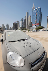 Skyline of skyscrapers and car parking lot on sand with abandoned car  in Dubai United Arab Emirates