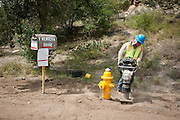 A construction laborer tamps dirt around a new fire hydrant as part of the Carnuel Water Systems Improvement Project on August 27, 2010. The $3.4 million project is supported by $2 million from the American Recovery and Reinvestment Act and will provide clean water to hundreds of Bernalillo County residents.