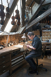 Craftsman making violin from wood