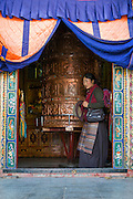 China, Tibet, Lhasa.  A local woman is spinning a huge Buddhist prayer wheel near the Potala Palace.