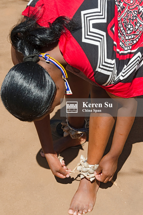 Swazi girl in traditional clothing putting on anklet, Mantenga Cultural Village, Swaziland