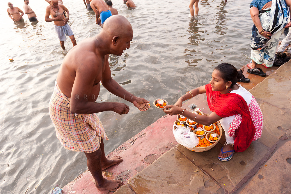 A man buys a candle prior to a ritual bath in the Ganges River, Varanasi, India. Photo ©robertvansluis.com