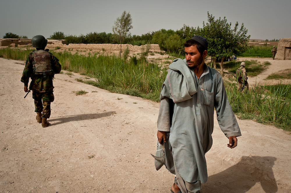 An Afghan farmer walks past an Afghan National Army soldier during a joint patrol.