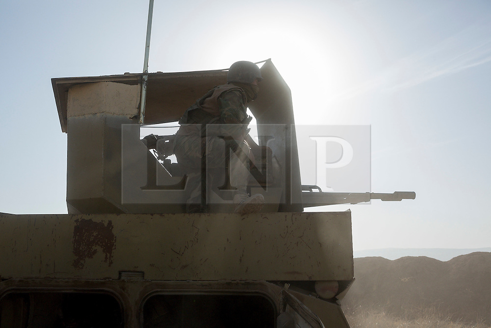 20/10/2016. Bashiqa, Iraq. A peshmerga gunner fires a heavy machine gun at ISIS positions as Kurdish forces start a large offensive to retake the Bashiqa area from Islamic State militants today (20/10/2016).<br /> <br /> Launched in the early hours of today with support from coalition special forces and air strikes, the attack is part of the larger operation to retake Mosul from the Islamic State, and involves both the Kurds and the Iraqi Army. The city of Bashiqa, around 9 miles north of Mosul, is one of several gateway areas that must be taken before any attempted offensive on Mosul itself.<br /> <br /> Despite the peshmerga suffering several casualties after militants fought back using mortars, heavy machine guns and snipers, the Kurdish forces were quickly taking ground with Haider al-Abadi, the Iraqi prime minister, stating that the operation to retake Mosul was progressing faster than expected. Photo credit: Matt Cetti-Roberts/LNP