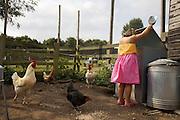 Charlotte, 6, feeding the chicken in the chicken run at Hares Farm. CREDIT: Vanessa Berberian for The Wall Street Journal<br /> UKFARM-Hares Farm