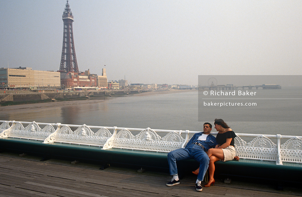 Young couple sit on an early, quiet Blackpool North Pier in Lancashire.