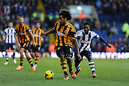 Hull city's Tom Huddlestone breaks away from WBA's Stephane Sessegnon. Barclays Premier league, West Bromwich Albion v Hull city at the Hawthorns in West Bromwich, England on Saturday 21st Dec 2013. pic by Andrew Orchard, Andrew Orchard sports photography.